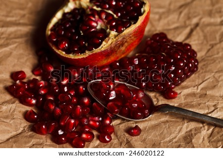 Pomegranate seeds and fruit with silver teaspoon on rustic paper - stock photo