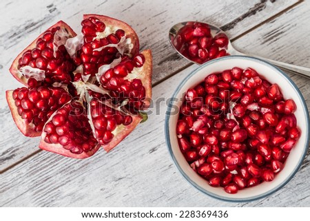 Pomegranate seeds in a plate and half pomegranate on a white wooden background - stock photo