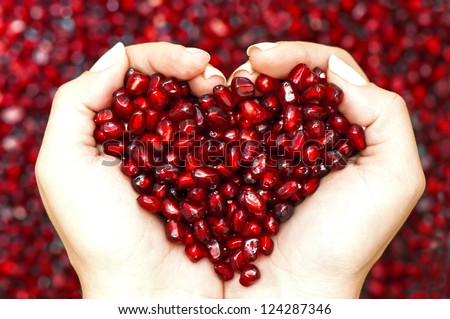 Pomegranate seeds in woman hands shaping heart symbol - stock photo