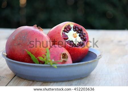 Pomegranates on Blue Pottery Dish 4 - stock photo