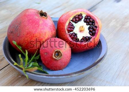 Pomegranates on Blue Pottery Dish 1 - stock photo