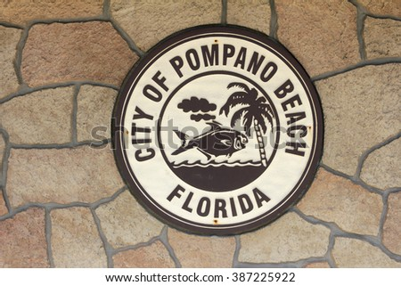 Pompano Beach, FL, USA - February 12, 2014: One brown and beige round City of Pompano Beach sign on a stone wall of the Hillsboro Lighthouse Museum building in the day - stock photo