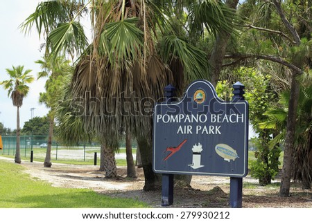 POMPANO BEACH, FL, USA - JUNE 21, 2014: Dark blue   Pompano Beach Air Park with City Of Pompano Beach, Florida. A red plane, white tower Goodyear blimp sign outside green fence guarding airport  - stock photo