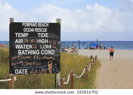 POMPANO BEACH, FLORIDA - DECEMBER 22, 2013: People enjoying themselves at Pompano Beach with an Ocean Rescue, beach conditions sign in front to the left in this mostly sunny Atlantic Ocean coast city  - stock photo