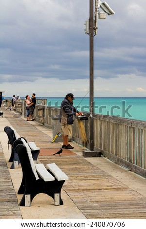 POMPANO BEACH, FLORIDA - JANUARY 26, 2011: Tourists and fishermen standing on the Pompano Beach Fishing Pier. The pier is always open and free for fishing.  - stock photo