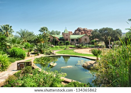 Pond and garden in front of old farm house. Shot in Namibia. - stock photo