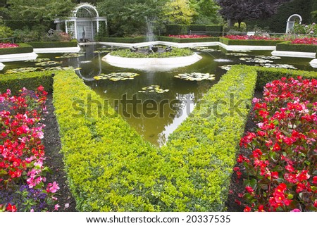 Pond, flower bed and a fountain in fine park in Canada