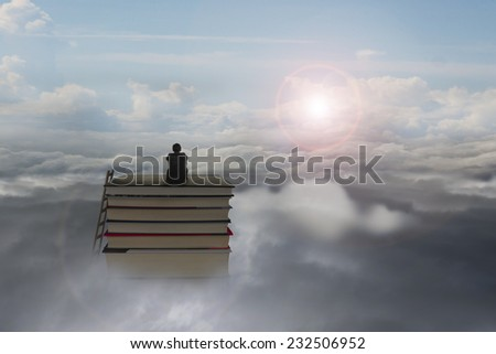 pondering businessman sitting on stack of books with sunlight sky cloudscape background
