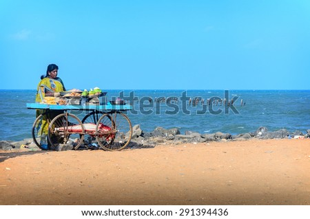 PONDICHERRY, INDIA - FEBRUARY 2, 2013: Unidentified Indian street vendor of  snacks with wheel cart on beach - stock photo