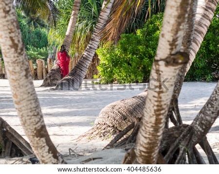 PONGWE, ZANZIBAR - APRIL 01, 2016: Masai warrior working as a security guard for one of the resorts talks on the phone on a beach.
