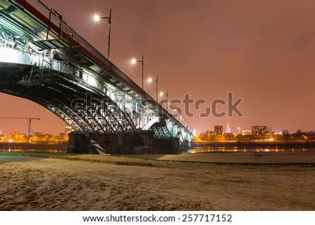 Poniatowski bridge over Vistula river illuminated at night in Warsaw, Poland - stock photo