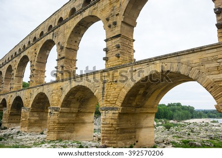 Pont du Gard, in Provence, France, over the Gardon river, is an 160 foot high roman aqueduct built to provide water to the city of Nimes from the river Eure near Uzes, in the first century A.D. - stock photo