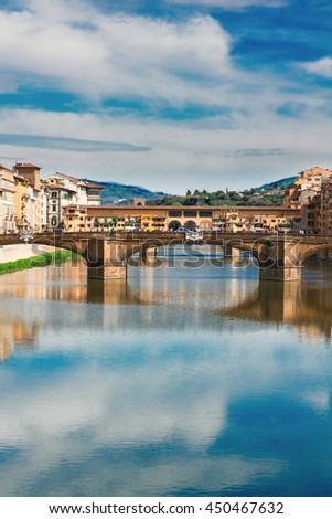 Ponte Santa Trinita bridge over the Arno River with cloudy sky and reflections, Florence, Italy - stock photo