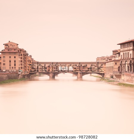 Ponte Vecchio medieval landmark on Arno river in a warm vintage mood taken through a 2 minute long exposure photography in a light foggy day. Florence, Tuscany, Italy. - stock photo