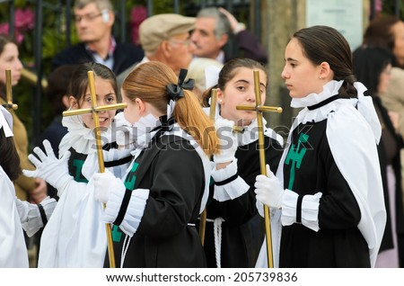 PONTEVEDRA, SPAIN - APRIL 17, 2014: A group of unidentified children carrying crosses, belonging to one of the religious brotherhoods, participating in the procession of Holy Week in the city center.