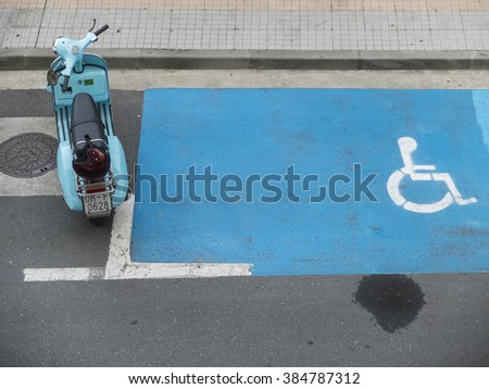PONTEVEDRA, SPAIN - APRIL 14, 2015: A motorcycle brand Vespa blue, next to a parking discapitados. - stock photo
