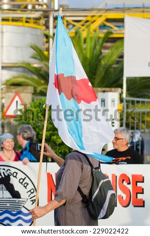 PONTEVEDRA, SPAIN - JUNE 21, 2014: A woman holding a flag of Galicia during a ecological demonstration against the permanence of paper pulp industry in the Ria de Pontevedra. - stock photo