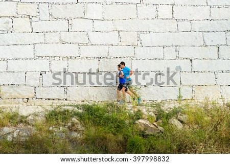 PONTEVEDRA, SPAIN - JUNE 28, 2015: Two young practicing sport in front of a large granite wall, along a path near the river in the city. - stock photo