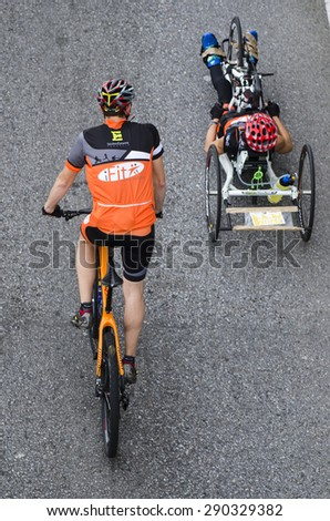 PONTEVEDRA, SPAIN - OCTOBER 19, 2014: A man and a woman cycling on a special bicycle for disabled, passes through one of the streets of the city, before a marathon. - stock photo
