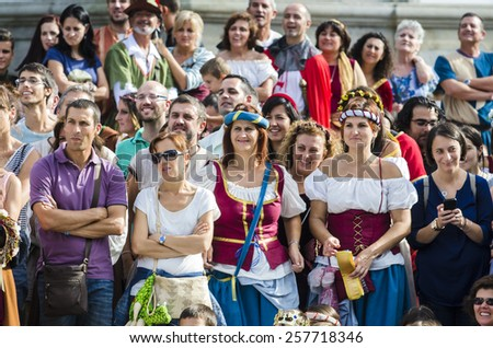 PONTEVEDRA, SPAIN - SEPTEMBER 6, 2014: People dressed in costumes from the Middle Ages, enjoy of a shows on the street, in medieval festival held each year in the historical district of the city. - stock photo
