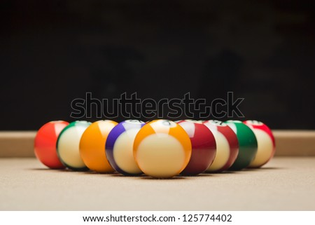 Pool balls arranged on pool table over dark background - stock photo