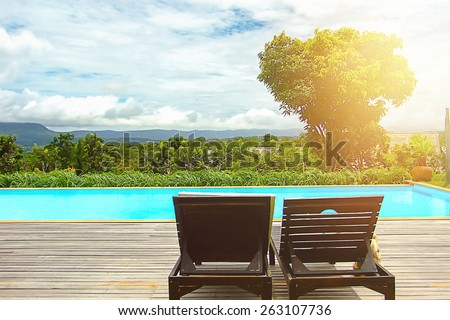 Pool beds on wooden ground  beside the public pool with light and mountain  in vintage style. - stock photo