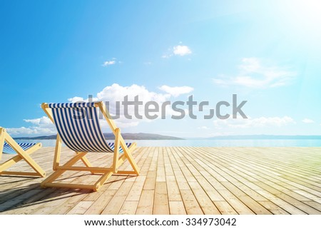 Pool deck with lounge chairs and view of sea - stock photo