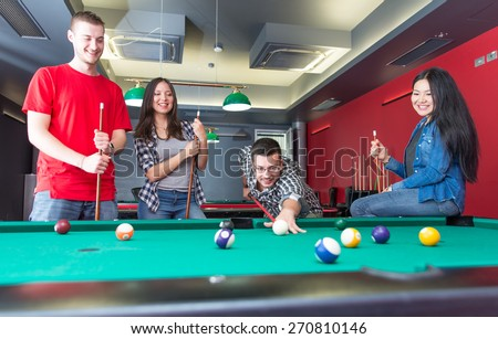 pool game. group of friends playing pool together. concept about fun, friendship,leisure and people - stock photo