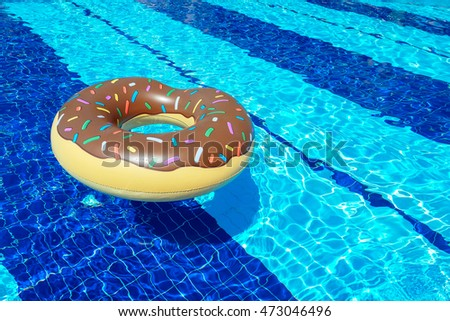 Pool inflatable in donut shape floating in a pool