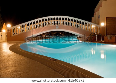 pool of Greek hotel with small bridge at night