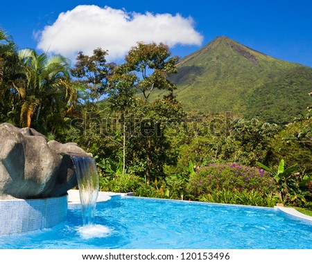 Pool with a view of the green side of Arenal Volcano, Costa Rica. - stock photo