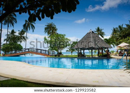 pool with artificial beach and tropical ocean