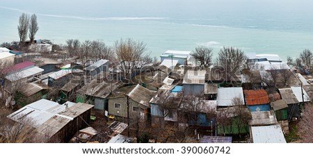 Poor and dirty slum by the sea - stock photo