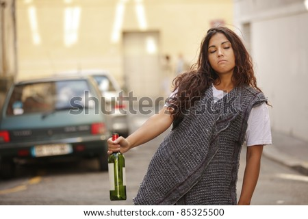 poor and drunk young girl  walking in city street - stock photo