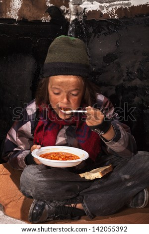 Poor beggar child eating charity food on the street sitting on cardboard plank - stock photo