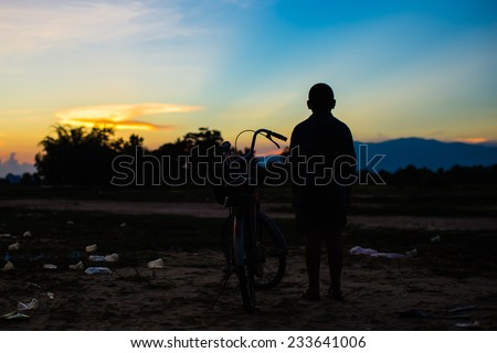 poor boy looking for a hope at the dirty garbage fields. - stock photo