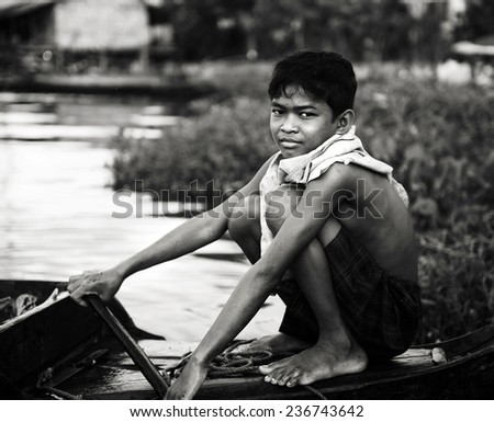 Poor boy on a boat. - stock photo