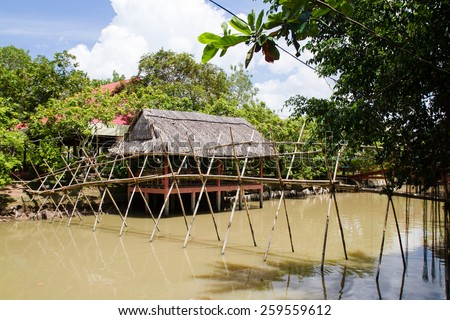 Poor cottage with arbour and a bridge in Mekong Delta, Vietnam - stock photo