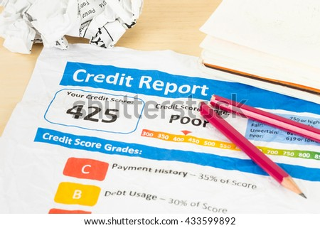 Poor credit score report on wrinkled paper with pen and calculator