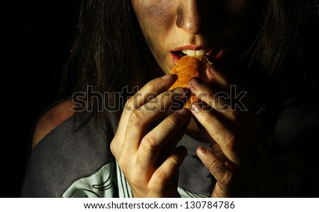 Poor dirty girl eating a piece of bread - stock photo