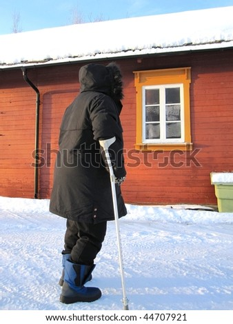 Poor fat disabled woman walking with a crutch in winter - stock photo