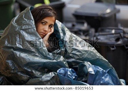 poor homeless young woman wrapped in plastic tarpaulin. - stock photo
