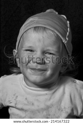 poor laughing child, black and white portrait on black - stock photo
