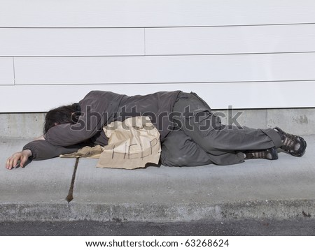 Poor man lying on sidewalk with help sign - stock photo
