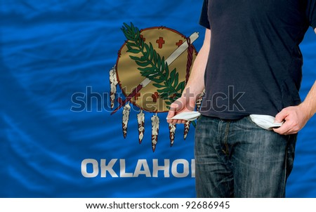 poor man showing empty pockets in front of american state of oklahoma flag - stock photo