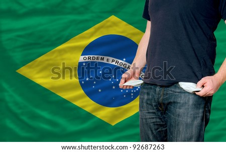 poor man showing empty pockets in front of brazil flag