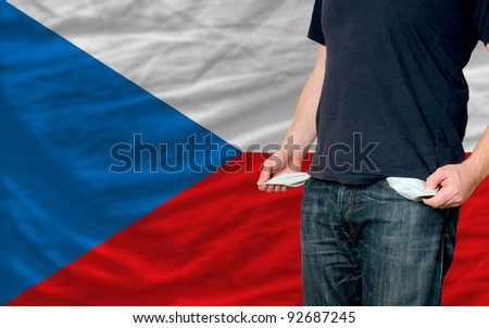 poor man showing empty pockets in front of czech flag - stock photo