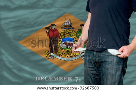 poor man showing empty pockets in front of delaware flag - stock photo