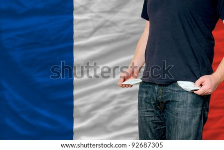 poor man showing empty pockets in front of france flag - stock photo