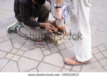 Poor shoe shiner - stock photo
